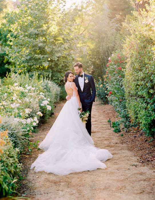 asian bride wearing a white wedding dress with a long train posing with her husband surrounded by lush green bushes and tress at the lodge in malibu lake captured by malibu wedding photographer dennis roy coronel