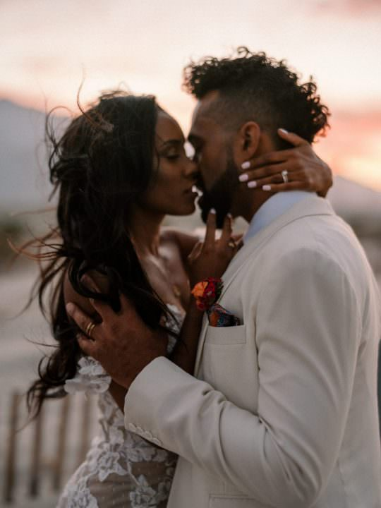 a black bride and groom embrace each other in a passionate kiss on their wedding day. The groom is wearing an ivory suit jacket while the bride wears a beautiful ivory laced wedding dress. They are at Palm Springs Sand Dunes during their covid wedding. Voted as a top wedding image of 2020 by INSIDER.