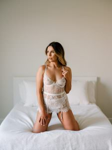 woman wearing three-piece white lingerie atop her bed on her knees