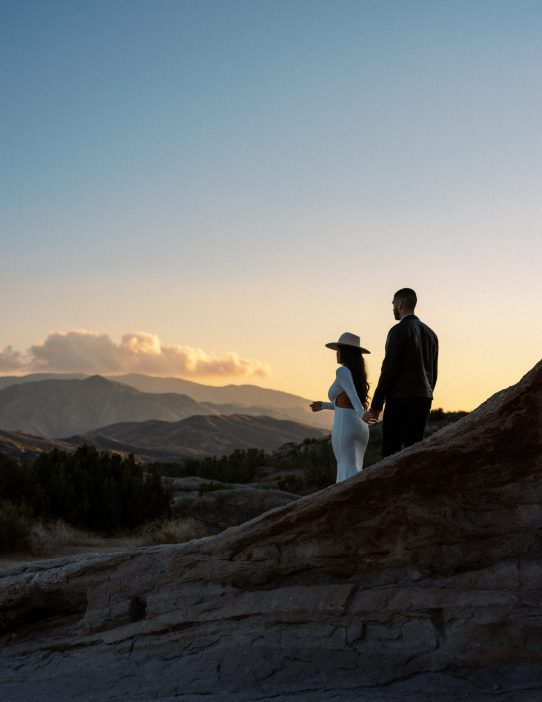 Bride wearing a backless white dress with an ivory fedora hat and groom in a black leather jacket are walking down a rock face during sunset at Vasquez Rocks Natural Area Park, California captured by Los Angeles wedding photographer Dennis Roy Coronel photography